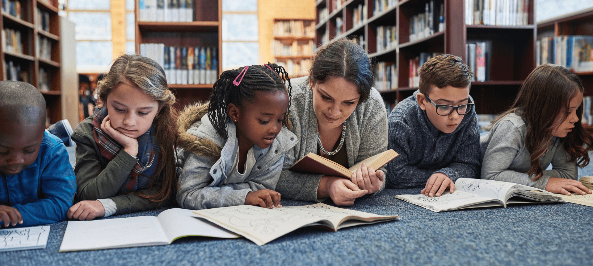 Female Teacher In Library With Elementary Students