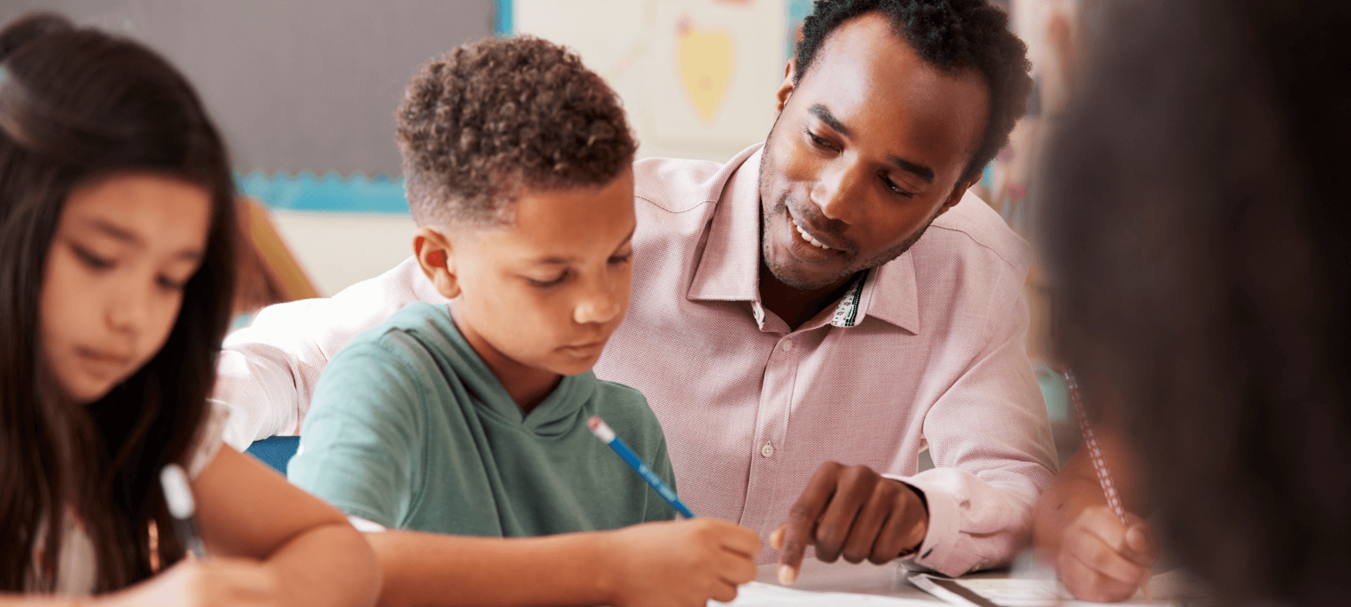 Male Teacher Working With Elementary Students